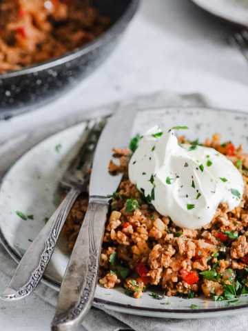 plate full of chorizo breakfast cauliflower rice hash topped with sour cream with knife and fork alongside