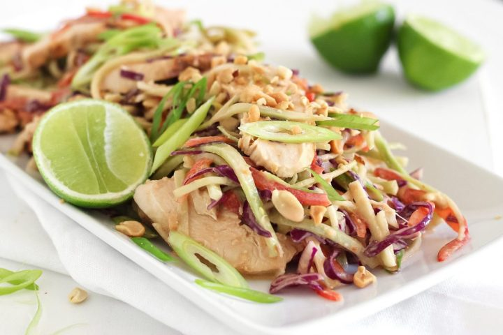 closeup photo of a plate with shredded broccoli red bell pepper and purple cabbage with sliced chicken in thai peanut curry sauce