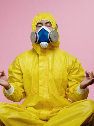 meditating man in yellow protective suit and mask