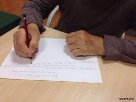 Paciente de daño cerebral escribiendo la receta de la semana del taller de alimentación