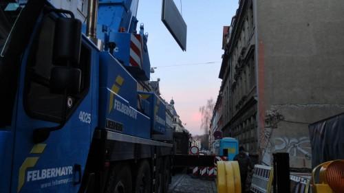 Mit schwerem Gerät werden die Platten für den Neubau transportiert.
