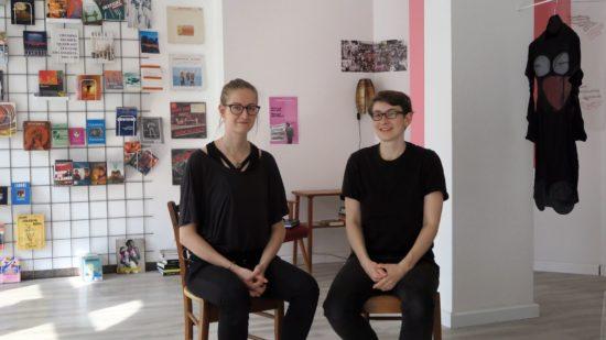 Anna Erdmann und Franziska Goralski vor dem großen Bücher- und Magazinregal und Textilarbeiten von Nada van Dalen aus Rotterdam