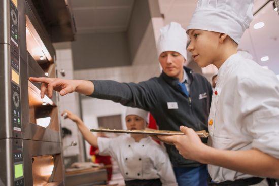 Rein in den Ofen - unter Anleitung haben die Kinder selbst gebacken - Foto: PR/Denise Kamps
