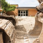 Heavy construction equipment moving dirt at school or government building.