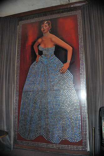 Large painting of women with dress made out of silver dollars
