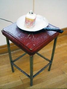 The Jimmy Durham Spilt Milk Fountain (Budget Version) // Box-steel Stool, Frying Pan, Water Pump, Cardboard Box, Wood, Paint, Milk Carton, Text, Digital Print // 210 x 35 x 35 cm // 2004