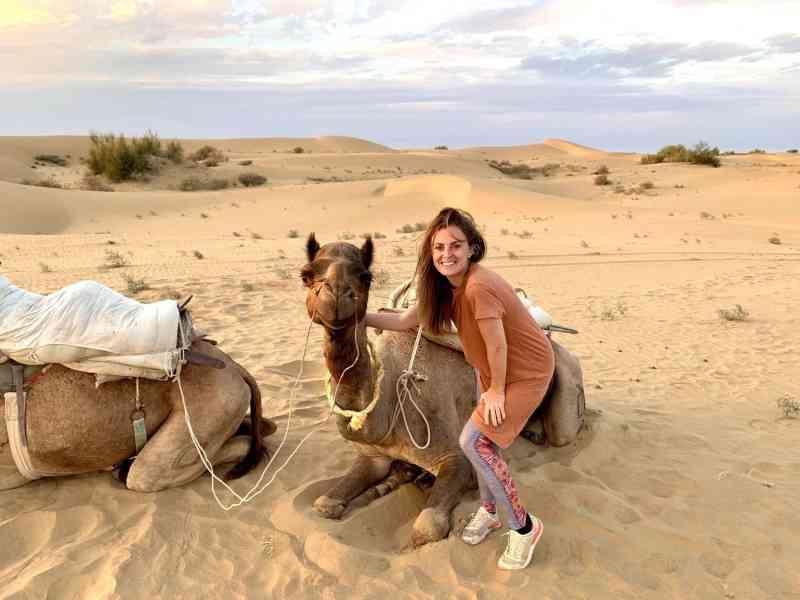Girl posing beside a smiling camel in the desert