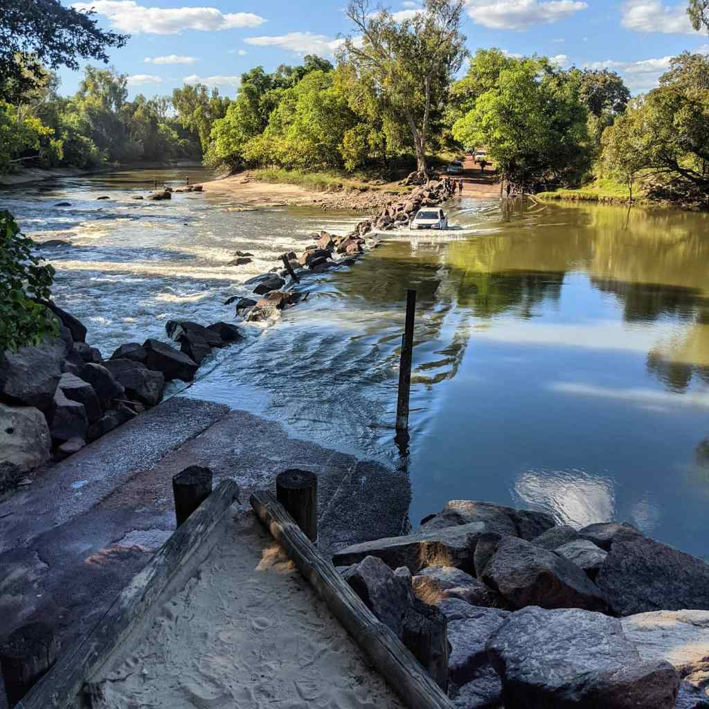 A car drives through fast flowing waters at a flooded crossing called Cahills Crossing, which is known for having saltwater crocodiles.