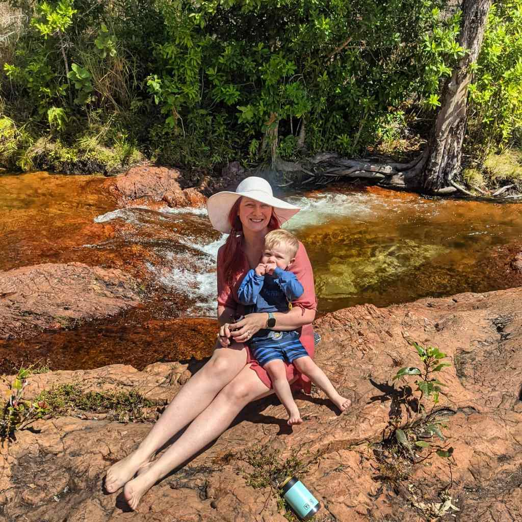 Mum and toddler pose on the rocks at Buley Rockhole in front of a flowing waterfall