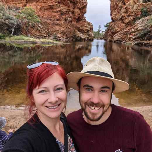 A couple, Jacqui and Daniel, stand in front of Ormiston Gorge in the West MacDonnell Ranges. The gorge is crystal clear water in a waterhole, surrounded by high rock cliffs.