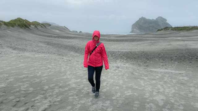 Erin wearing Allbirds wool runners on a chilly, drizzly walk on Wharariki Beach in New Zealand