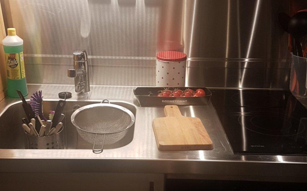 bilde viser et kjøkken i krom, vaske med en bestikkurv og en sil i, på det tjue cm med kjøkkendisk ligger det et skjærebrett, noen tomater og en boks med prikker på, til høyre i bildet er en platetopp.