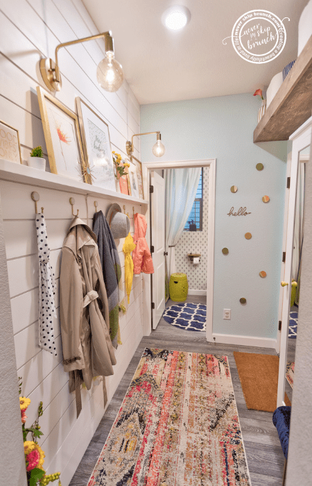 Mudroom Reveal — narrow room with a colorful rug, shiplap accent wall, storage hooks under picture frame, and wooden floating shelves. Bright and colorful mudroom decor