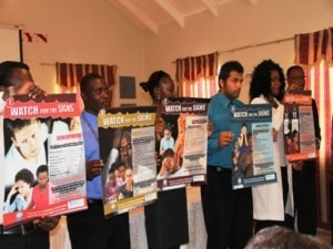 Deputy Premier and Minister of Health in the Nevis Island Administration Hon. Mark Brantley (extreme right) looks on as Windsor University School of Medicine students display posters related to various signs of mental illnesses
