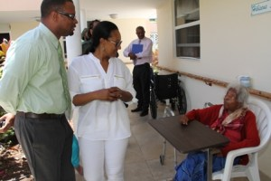 Deputy Premier of Nevis and Founder of Tender Care International Mrs. Judith O'Loughlin-Lescott with 103-year-old Flambouyant Nursing Home resident Ms. Jane Canning during a tour of the Home and the Alexandra Hospital with international reggae artistes Duane Stephenson and Droop Lion