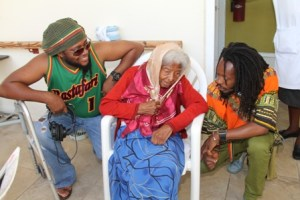 International reggae artistes (l-r) Duane Stephenson and Droop Lion show fascination with103-year-old Flambouyant Nursing Home resident Ms. Jane Canning