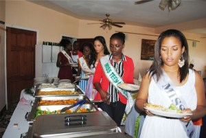 : Lunch is served: Miss St. Kitts, Pernelle Abraham, and behind her, Miss Montserrat, Vanice Tuitt, and others by the buffet table.