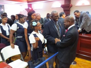 Lecturer at the Clarence Fitzroy Bryant College (CFBC) and former Minister in the PAM Administration, Mr. Hugh Heyliger congratulates St. Kitts and Nevis' Prime Minister and Minister of Finance, the Right Hon. Dr. Denzil L. Douglas (right) on the presentation of the 2014 Budget while students of the Economics Class look on.