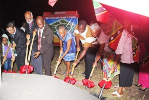 Turning the sod to break ground: From left, a child from the community, Ambassador Tsao, Governor General His Excellency Sir Edmund Lawrence, Prime Minister, the Rt Hon Dr Denzil Douglas, Minister the Hon Marcella Liburd, members of the New Road community Mr Sherwin Whyte, Mrs Ingrid Richards, and a community members who is partly hidden.