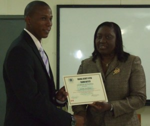 Permanent Secretary Ambassador Astona Browne presents certificate to RSCNPF Constable Lowell Wallace