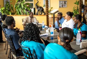 Prime Minister Denzil Douglas sits with staff of the Royal St. Kitts Hotel