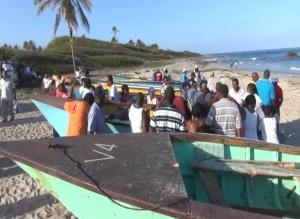 Members of the public gather round the fishing boats to purchase fish caught during the Hanley's Road Fisherfolk Association's Inaugural Fishing Tournament at the Indian Castle Beach on May 05, 2014
