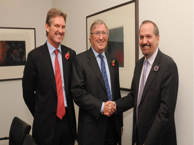 CONGRATULATIONS : Chairman of Cable and Wireless Communications (CWC), Sir Richard Lapthorne (centre) congratulates Chairman and CEO of Columbus International Inc. Brendan Paddick following the announcement of the proposed merger between CWC and Columbus in London today. Looking on is Phil Bentley, CEO of CWC.