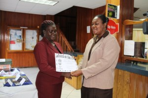 "Customer Service Manager at the Nevis Post Office Carol Jeffers (r) presents ""Officer of the Year"" award for 2014 to Marva Morton-Parris at the Charlestown Post Office"