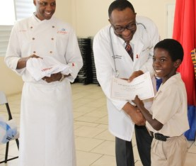 Head of the Rouse Foundation, Cardiologist Dr. Charlie Rouse and Celebrity Chief of Atlanta Marvin Woods, distribute Certificates of Participation and chief gear to students of the Charlestown Primary School for their participation in the Mini Chief Academy on February 24, 2015