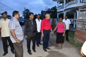 President Donald speaking with a Rose Hall, Berbice resident during a walk about on March 25, 2015