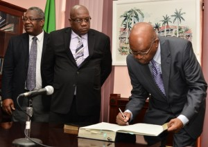 Acting Governor General Seaton signs the legal documents while Prime Minister Harris looks on as Attoney General Vincent Byron shares pleasantries with other Cabinet members