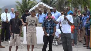 Head of the Nevis Turtle Group Lemuel Pemberton (front row left) delivering remarks at the release of sea turtle Millie on the beach outside the Four Seasons Resort on Nevis on July 13, 2015 praising young volunteers in his group (l-r) Stedroy Sturge and brothers Jaleel and Jevaunito Huggins