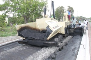 Nevis Public Works Department workers applying the first layer of asphalt concrete on Hanley's Road during the Hanley's Road Rehabilitation Project on October 09, 2015