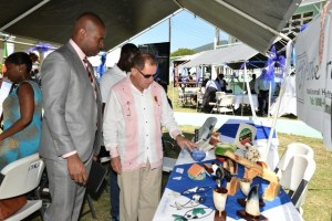 Minister Richards pays keen attention as an exhibitor explains the contents in his booth.