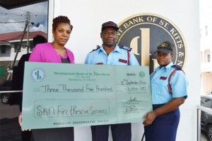 FSSO Elvis Isaac and WFO Chenelle Bart receive sponsorship cheque for Miss Basseterre Fire Station from Ms Vernitha Maynard, Marketing Officer at the Development Bank of St. Kitts and Nevis.