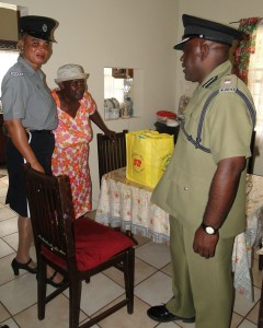 Ms Iris Browne of Zion Village recieving a gift basket from officers of the Nevis Division as part of Police Week Celebrations.