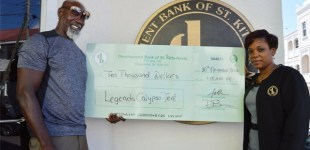 Mr Sylvester Hodge, better known in calypso circles as King Socrates, receives a sponsorship cheque for Legends Calypso Tent from Development Bank's Marketing Officer, Ms Vernitha Maynard.