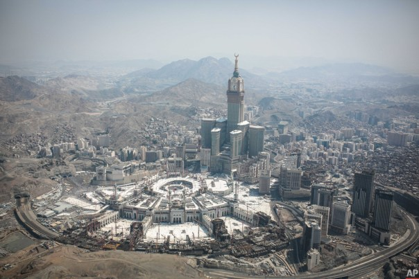 In this aerial photo made from a helicopter, The Abraj Al-Bait Towers with the four-faced clocks stands over the holy Kaaba, as Muslims encircle it inside the Grand Mosque, during the annual pilgrimage known as the hajj, in the Muslim holy city of Mecca, Saudi Arabia, Friday, Sept. 25, 2015. (AP Photo/Mosa'ab Elshamy)