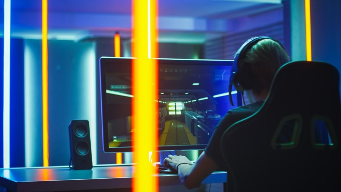 Pro Gamer Plays in the First Person Shooter on His Personal Computer. Talks with Teammates through Headphones. Neon Colored Room. Online eSport Tournament in Action.