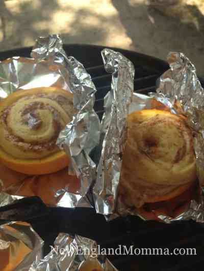 Place one cinnamon roll into each orange rind and place on a sheet of tin foil for cooking on the grill.