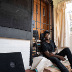 13 November 2018: Artist Shumba Felix sitting in front of the first artwork of 'Series in Blackness.'