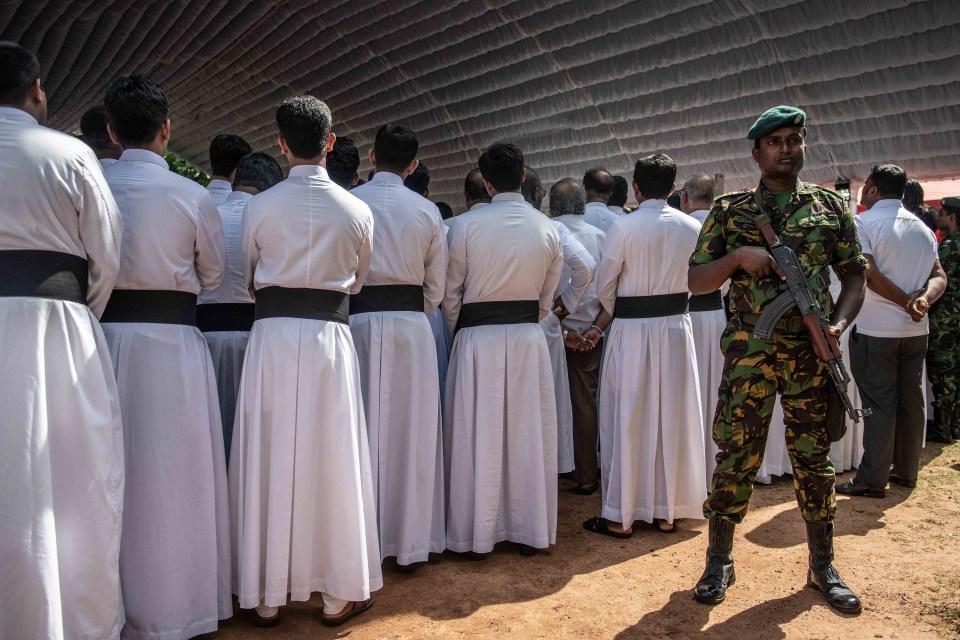 23 April 2019: A soldier stands guard behind Catholic priests and other clergy members during a mass funeral at St Sebastian's Church in Negombo. Sri Lankan authorities declared a state of emergency on Monday. (Photograph by Carl Court/Getty Images)