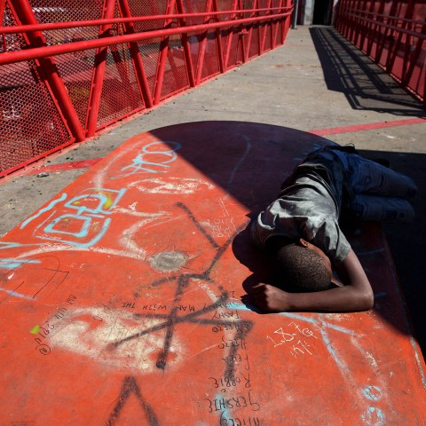 2 October 2018: A boy of around 12-years-old lies passed-out on a pedestrian bridge in Westbury after taking drugs. The Westbury community protested against gang violence and drugs last week. Photograph by James Oatway