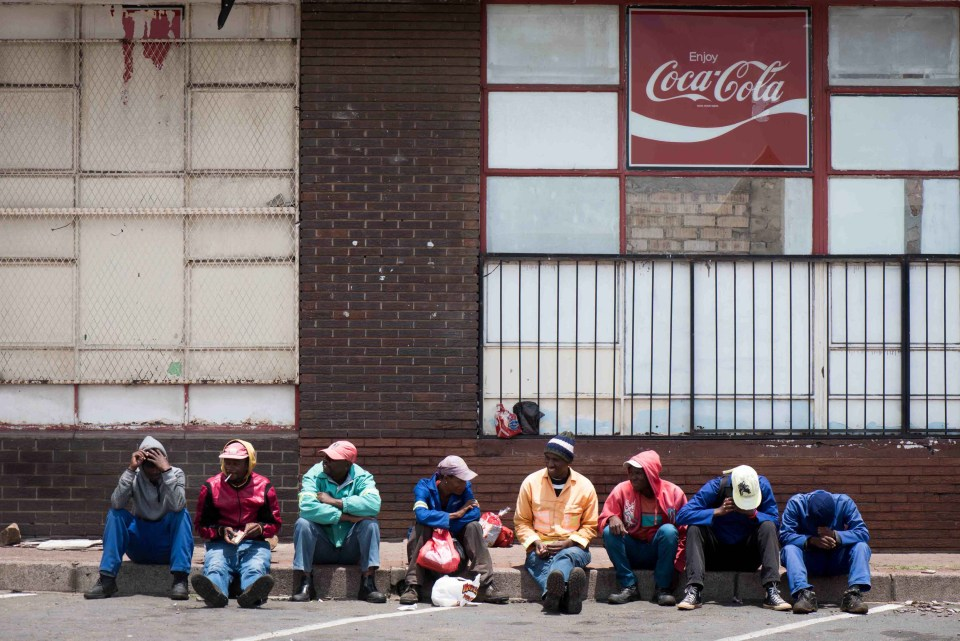 2 November 2018: Unemployed men sit on a street corner, in central Middelburg, looking for casual labour opportunities.