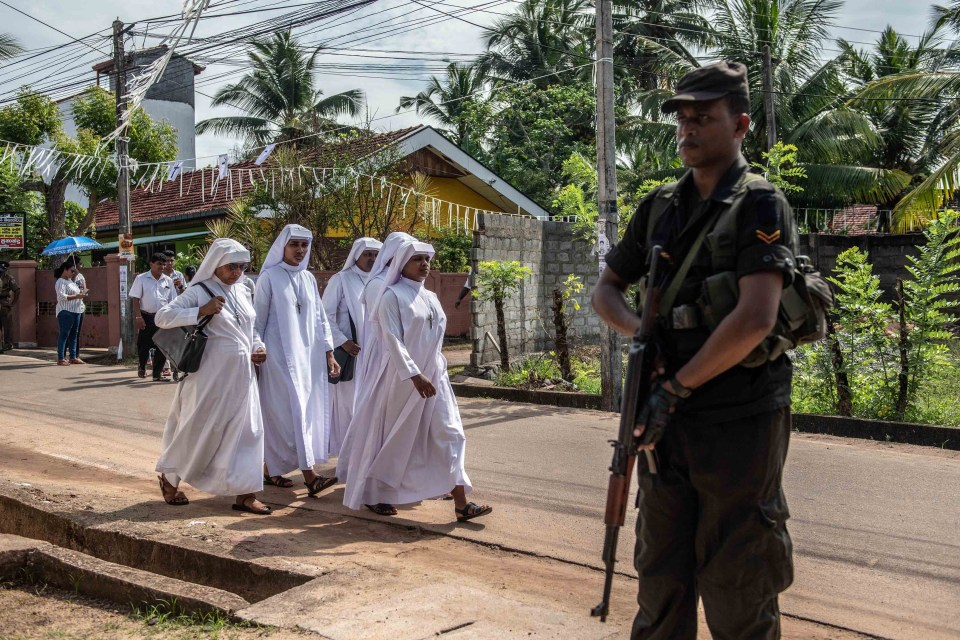23 April 2019: A soldier stands guard as nuns walk past to attend a mass funeral at St Sebastian Church in Negombo, Sri Lanka. At least 321 people were killed after attacks on churches and hotels on Easter Sunday. (Photograph by Carl Court/Getty Images)