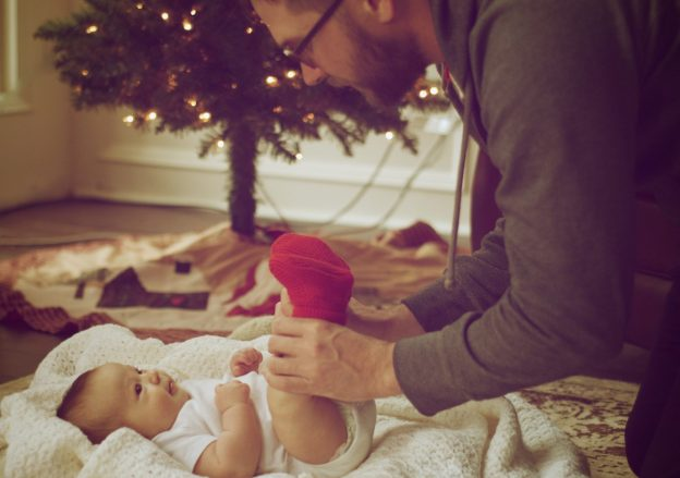 Dad changing baby in front of a christmas tree - birth partner tips