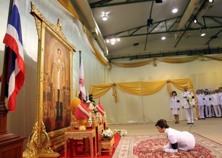 Thailand's first female PM Yingluck Shinawatra pays respect as she receives the royal command appointing her as the country's new premier in front of a portrait of Thai King Bhumibol Adulyadej in Bangkok