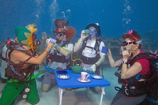 """Divers including from left, Katie Jennele, Bob Rowland, Eric Rolfe and Alicia Merel act out an """"Alice in Wonderland"""" underwater tea party at the Underwater Music Festival in the Florida Keys National Marine Sanctuary Saturday, July 10, 2010, near Big Pine Key, Fla. The annual subsea concert attracted more than 500 divers and snorkelers to listen to a local radio station's broadcast piped beneath the sea with underwater speakers. (Bob Care/Florida Keys News Bureau)"""