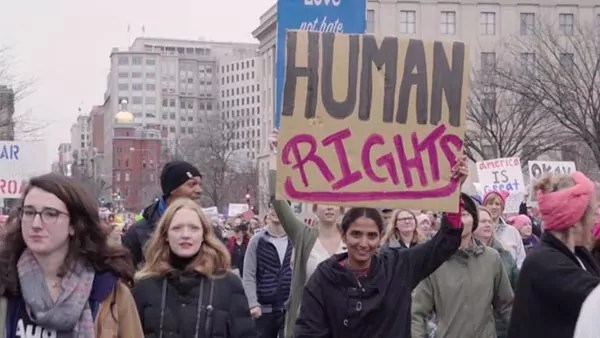 """Protestors march, with one holding up a sign reading """"HUMAN RIGHTS""""."""