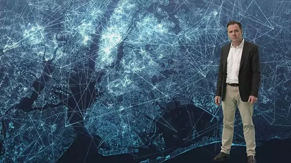 A person stands in front of a map of New York City colored in blue and filled with network lines.